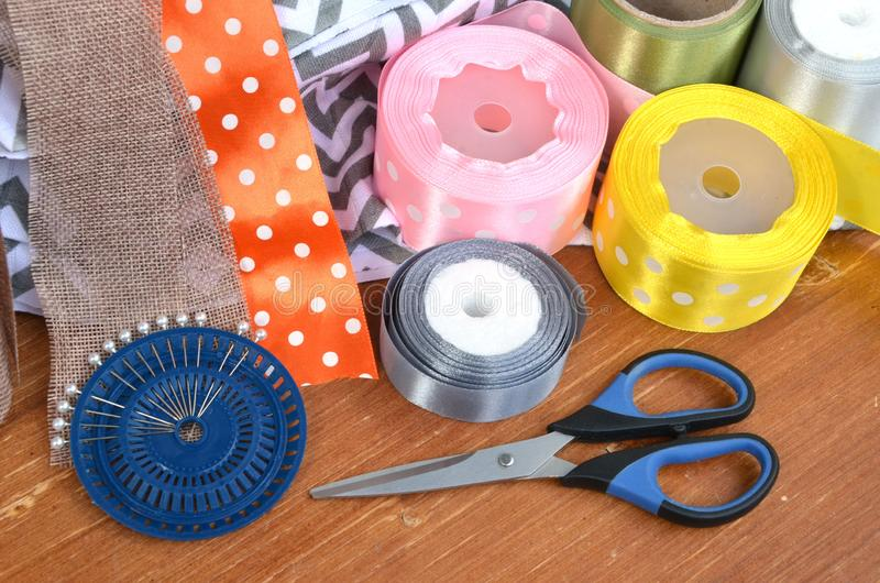 Color ribbons, scissors and pins set on wooden plank royalty free stock photos