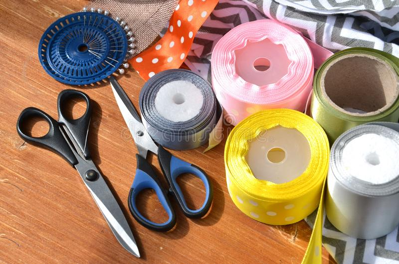 Color ribbons, scissors and pins set on wooden plank stock photos