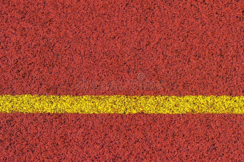 Color rojo estándar de goma de la pista corriente y línea amarilla fotografía de archivo libre de regalías