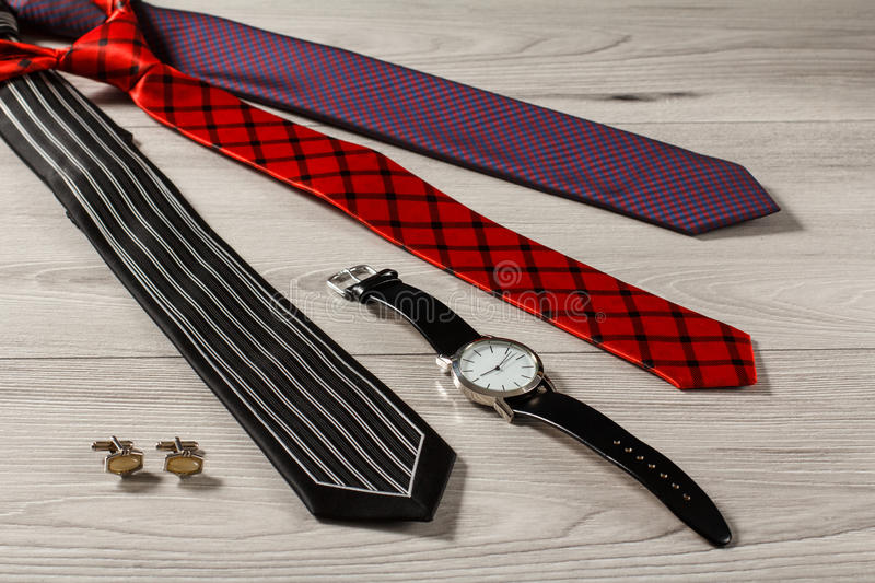 Color silk neckties, watch, cuff-links on a gray wooden background. Color silk neckties, watch with a leather strap, cuff-links on a gray wooden background stock photography