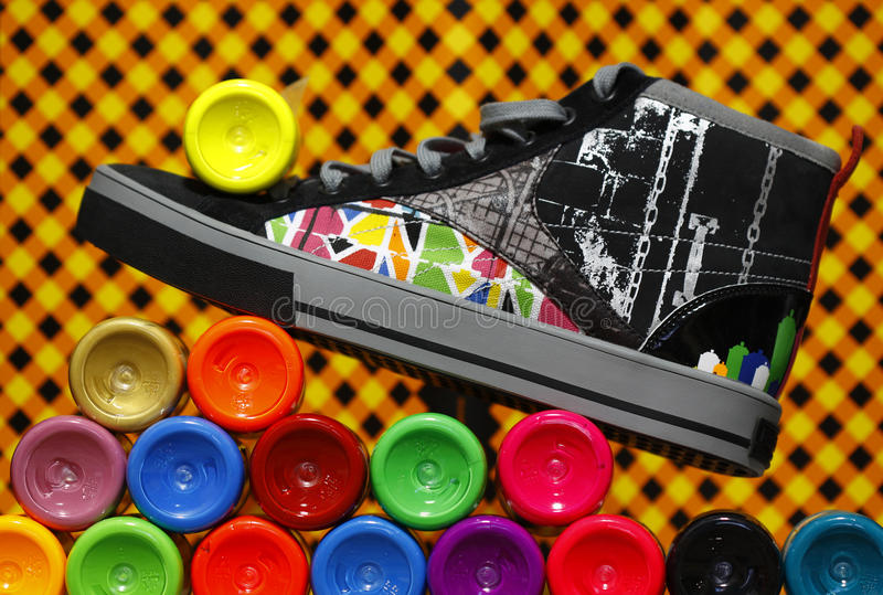 Color sneaker standing on paint bottles royalty free stock photography