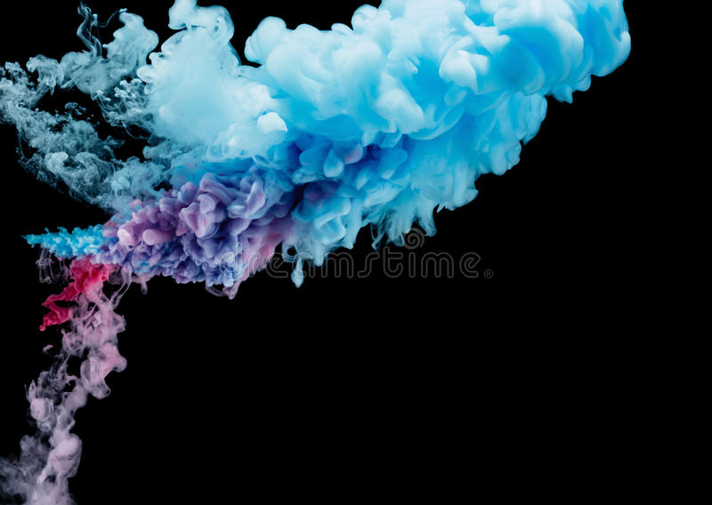 Color splashes of ink isolated on black background. Abstract paint in water motion. Swirling colorful drops royalty free stock photography
