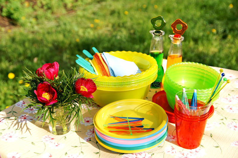 Color summer picnic accessories on a lawn. A table with bright multicolor summer picnic party plastic accessories, plates and dishes, napkins, bottles and stock photos