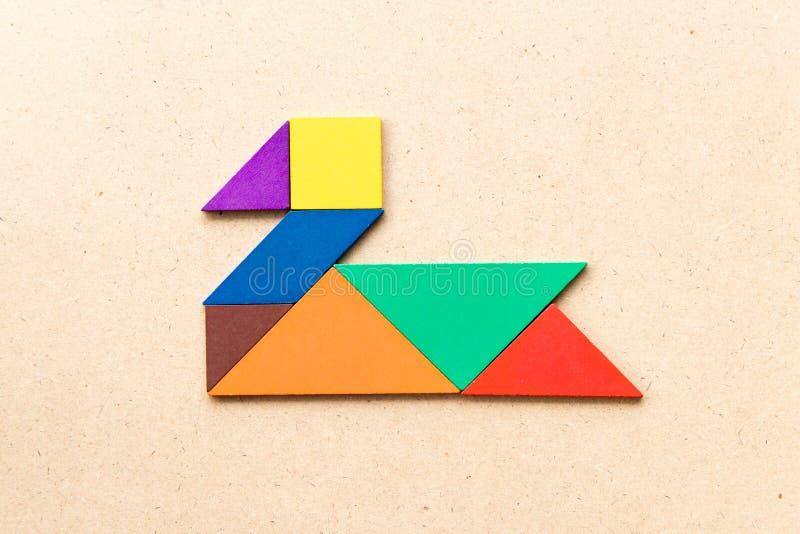 Color tangram in swan or duck shape on wood background. Color tangram puzzle in swan or duck shape on wood background royalty free stock photos