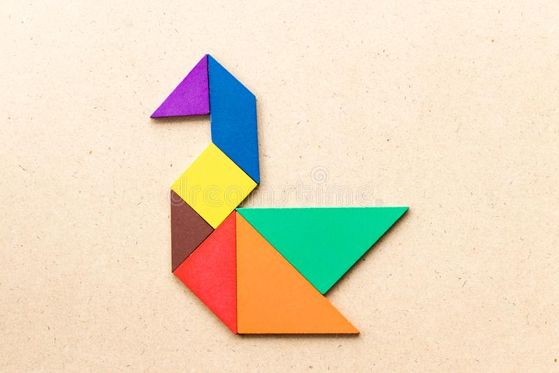 Color tangram in swan or duck shape on wood background. Color tangram puzzle in swan or duck shape on wood background royalty free stock photo
