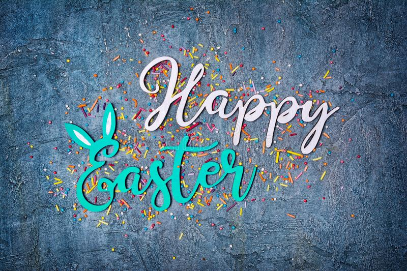 Color text of happy easter with sugar sprinkles or confetti as decor for bakery. Top view on bright text of happy easter with sugar sprinkles or confetti as stock photos