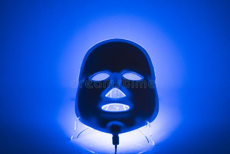Color therapy mask glowing on a blue background. Color therapy electric led lighting mask glowing blue on a blue background royalty free stock photo