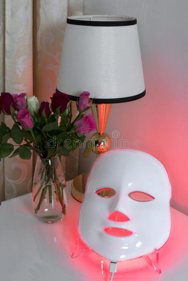 Color therapy mask, vase with roses and a lamp. Color therapy mask glowing red on the table, a glass vase with roses of different colors and a table lamp royalty free stock image