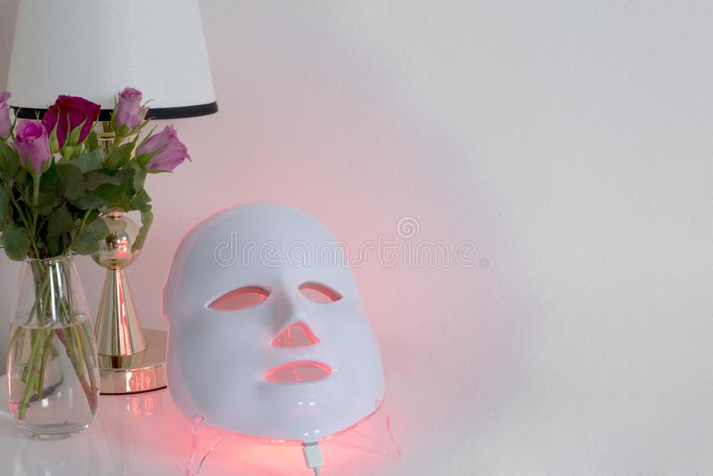 Color therapy mask, vase with roses and a lamp. Color therapy mask glowing red on the table, a glass vase with roses of different colors and a table lamp royalty free stock photo