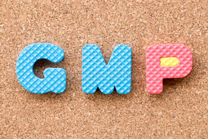 Color toy foam alphabet in word GMP & x28;Abbreviation of Good Manufacturing Practice& x29; on cork board background royalty free stock images
