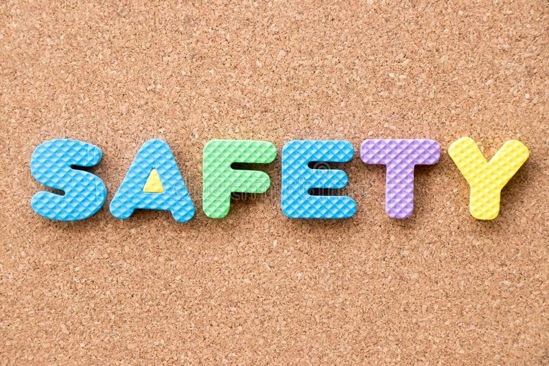 Color toy foam alphabet in word safety on cork board stock image