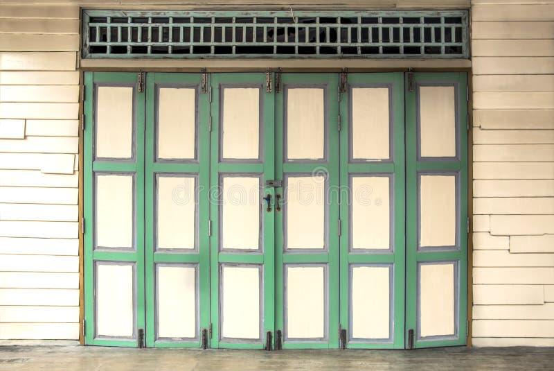 Color verde de las puertas de madera dobles del vintage en el viejo yel de madera de la pared foto de archivo libre de regalías