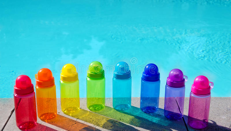Color water bottles by the pool. Color water bottles by the swimming pool in sunny day royalty free stock photo