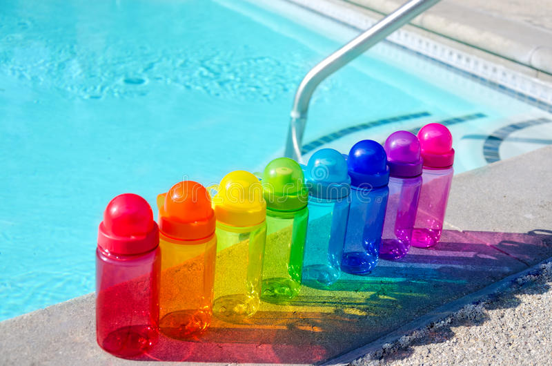Color water bottles by the pool. Color water bottles by the swimming pool in sunny day royalty free stock images