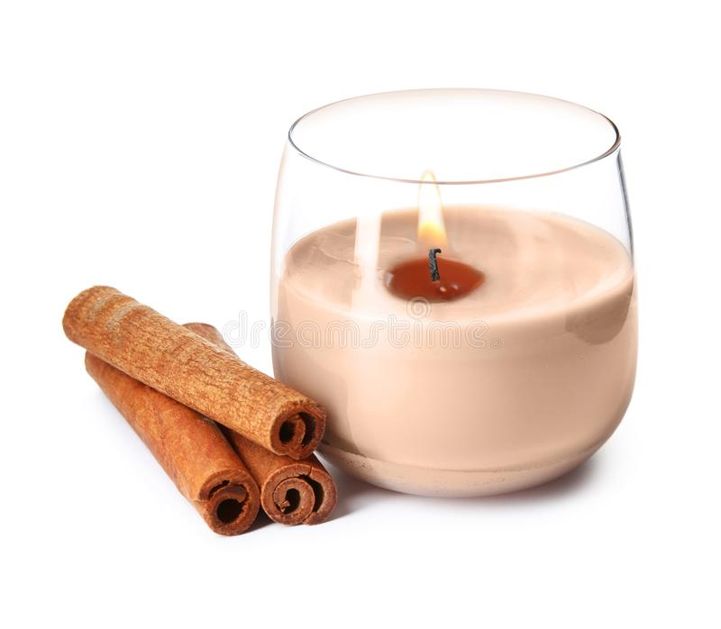 Color wax candle in glass holder and cinnamon sticks isolated. On white stock image