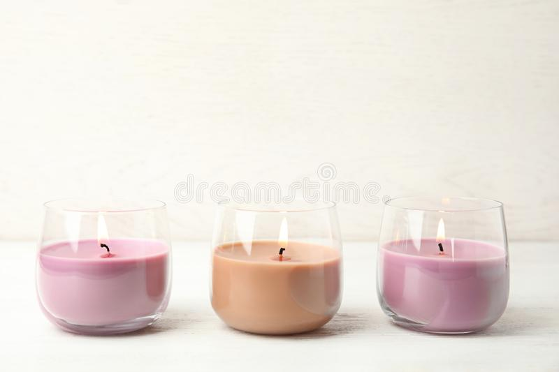Color wax candles in glass holders on white table, space for. Text royalty free stock images