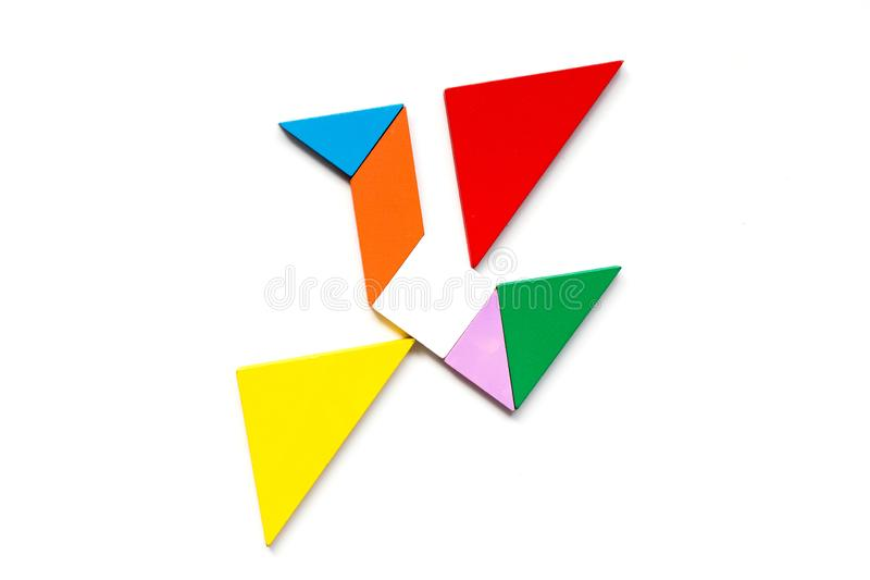 Color wood tangram puzzle in flying bird shape on white background. Game, art, concept, abstract, geometric, creative, board, element, grunge, colorful, card royalty free stock photography