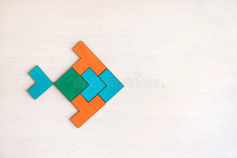 Color wooden tangram puzzle in fish shape. Color wooden tangram puzzle in fish shape on white wood background stock image