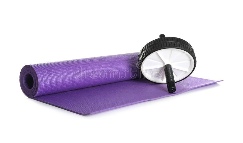 Color yoga mat and roller wheel on white background stock image