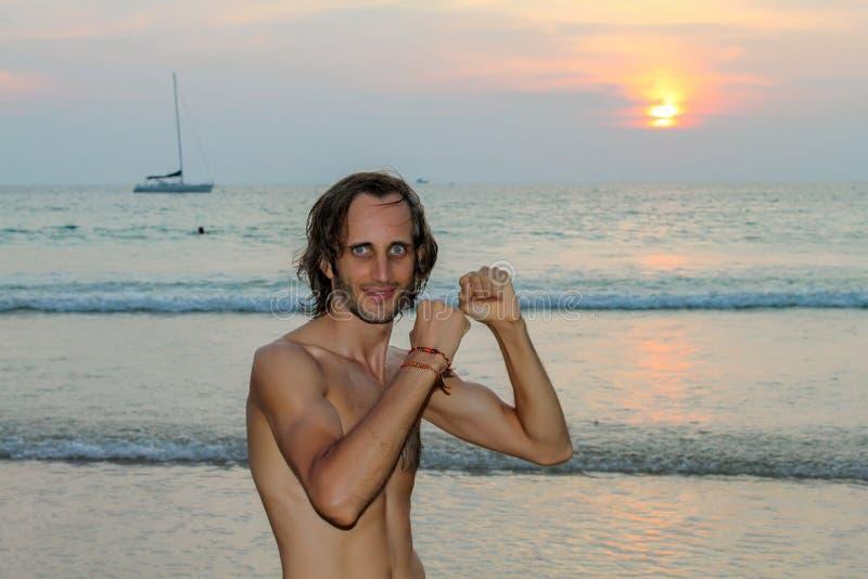 Colora a foto do retrato do homem considerável que olha acima e que sorri durante o por do sol na praia imagens de stock