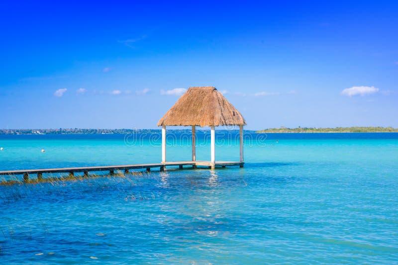 Colora a imagem classificada de um cais com nuvens e água azul no Laguna Bacalar, Chetumal, Quintana Roo, México fotografia de stock royalty free