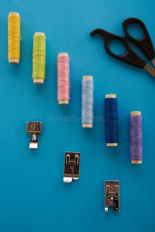 colora a linha, as tesouras e costurar os elementos sobre um azul fotos de stock