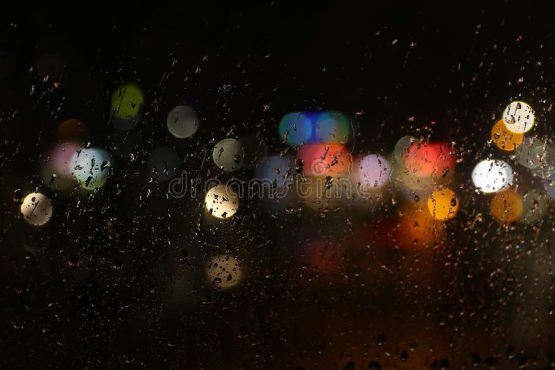 Colora luzes no vidro de janela escuro chuvoso imagens de stock