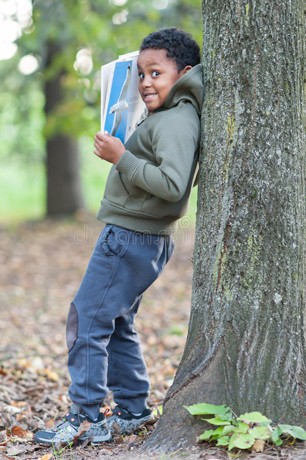 Colora o bebê que inclina-se contra uma árvore que lê um livro foto de stock royalty free