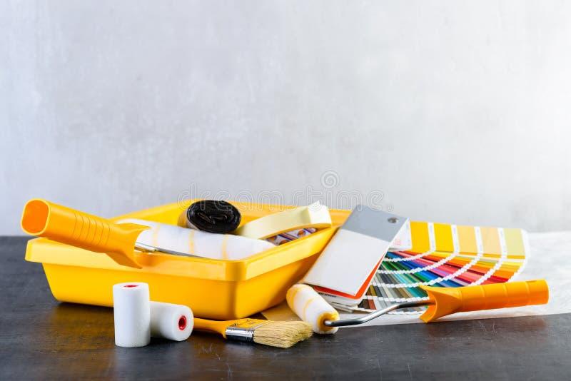 Colora o catálogo das amostras, a escova, a bandeja da pintura e os rolos de pintura, diff imagem de stock