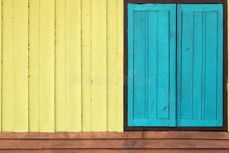 Colora a parede e a janela de madeira alaranjadas azuis amarelas fotografia de stock royalty free