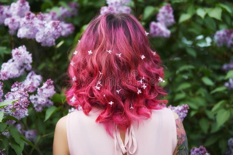 Coloración del cabello del maquillaje en pelo rojo, rosado brillante de la muchacha con las flores de la lila Color saturado bril imágenes de archivo libres de regalías