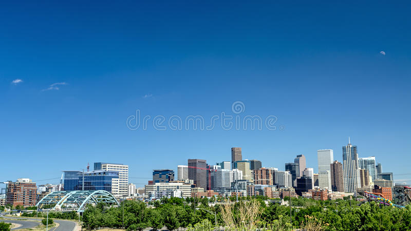 Colorado City of Denver with a half moon in the sky stock photography