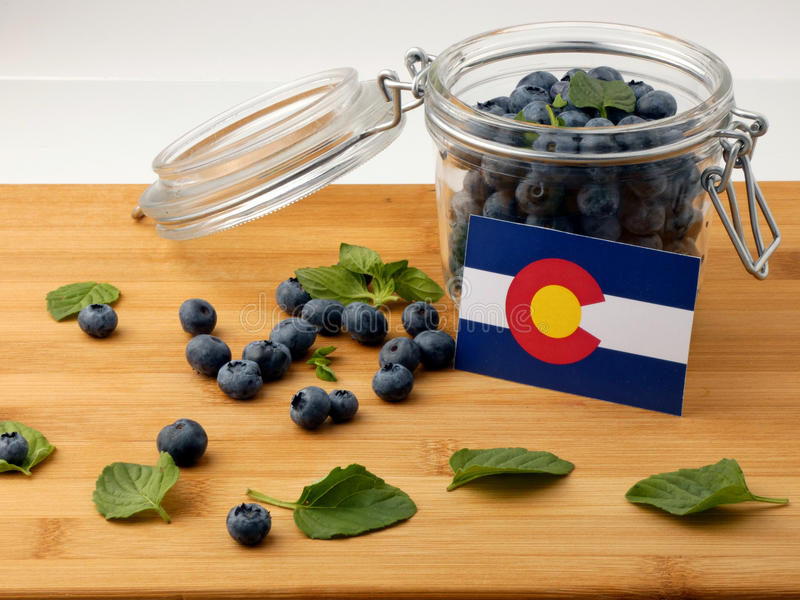 Colorado flag on a wooden plank with blueberries on whi. Te royalty free stock photos