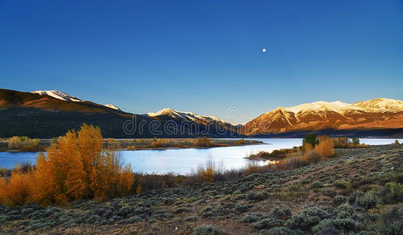 Colorado Mountain sunrise on the Twin Lakes. Colorado Mountain on the Twin Lakes near Leadville Colorado. Moon is still clear after sunrise in autumn stock photos