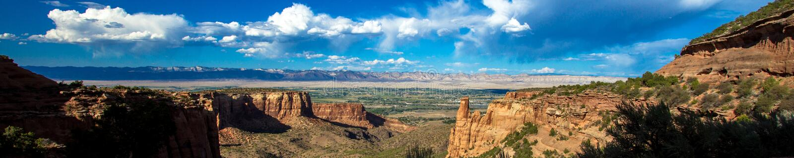 Ultra-wide panoramic view looking east toward Grand Junction from Colorado National Monument. An ultra-wide panorama shows the vast skies, steep canyons, and royalty free stock image