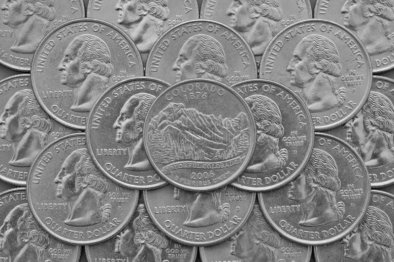 Colorado State and coins of USA. Pile of the US quarter coins with George Washington and on the top a quarter of Colorado State royalty free stock photo