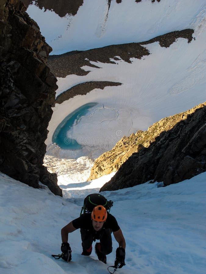 A man climbs up a glacier, Colorado Rocky Mountains. Colorado, USA - 6/27/15 - A man climbs up a couloir in the Elk Range, Colorado Rocky Mountains royalty free stock images