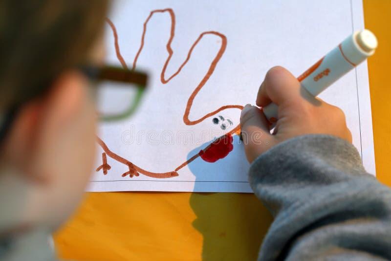 Colorante de la mano del niño con el marcador fotografía de archivo libre de regalías
