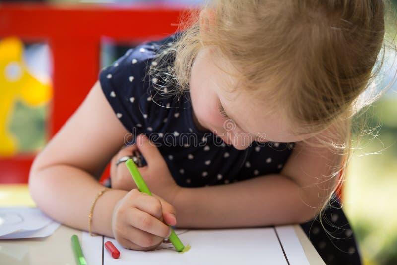 Colorante de la muchacha con el pastel foto de archivo