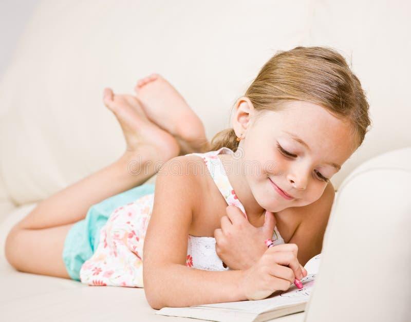 Colorante de la muchacha en libro de colorante foto de archivo libre de regalías