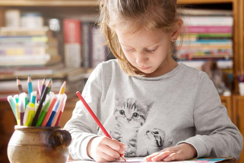 Colorante de la muchacha en un libro de colorear fotos de archivo libres de regalías