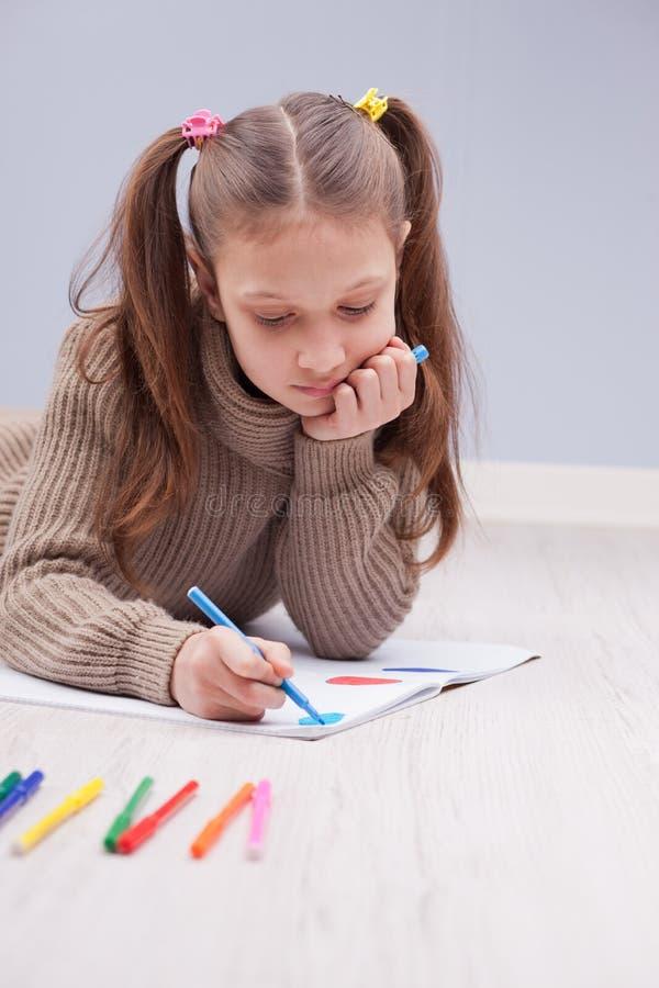 Colorante de la niña en su cuaderno foto de archivo
