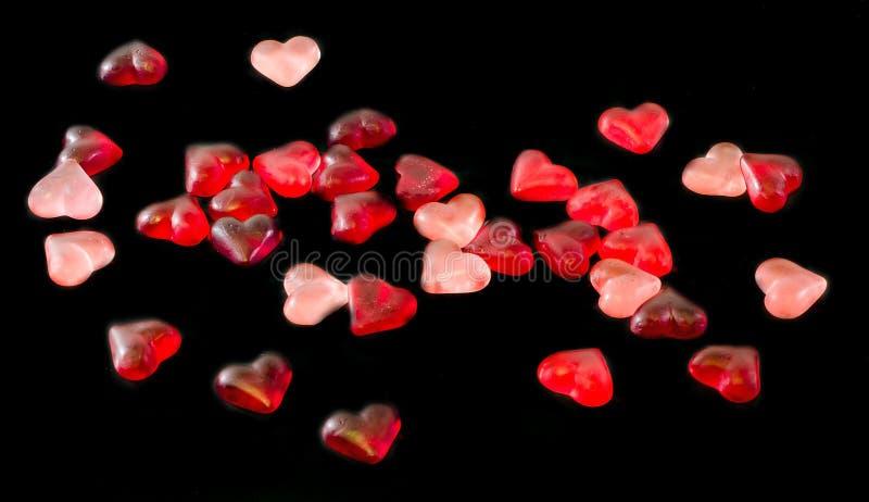 Colorato (rosa, rosso ed arancio), gelatine trasparenti di forma del cuore, fondo nero immagine stock libera da diritti