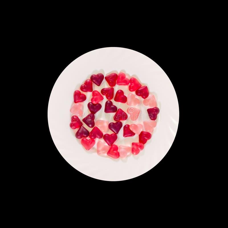 Colorato (rosa, rosso ed arancio), la forma trasparente del cuore si gelatinizza con il piatto ceramico, fondo nero, isolato fotografia stock