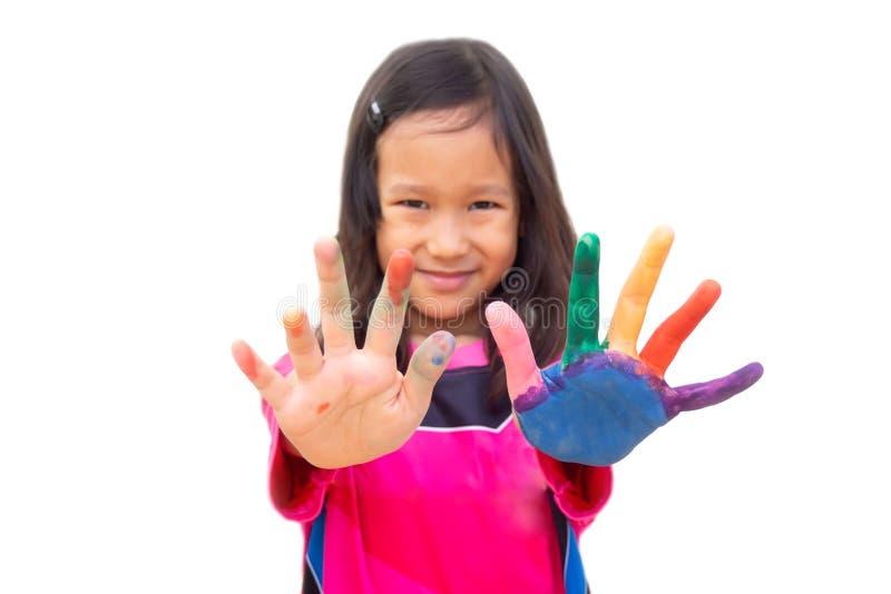 Colore asiatico della pittura della ragazza sulla mano sinistra e sul dito Attività di arte fotografie stock