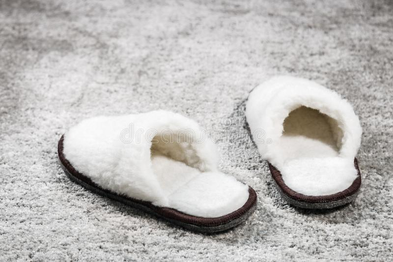 Colore bianco delle pantofole domestiche simili a pelliccia sul tappeto fotografia stock
