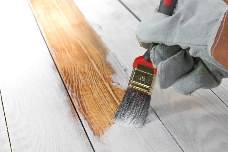 Colore bianco di verniciatura della spazzola della tenuta della mano su legno fotografia stock libera da diritti