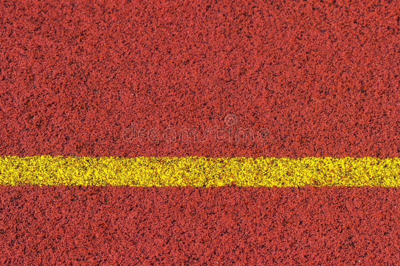 Colore rosso standard di gomma della pista corrente e linea gialla fotografia stock libera da diritti