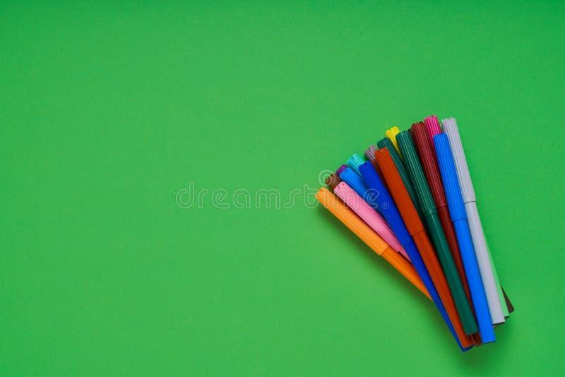 Coloreado sentía plumas de extremidad en el fondo verde de neón con el lugar para el texto Visi?n superior imágenes de archivo libres de regalías