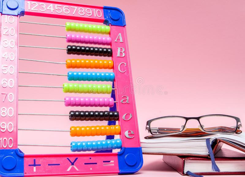 Colored Abacus, Glasses and Notebook on pink background. Education, back to school concept stock photo